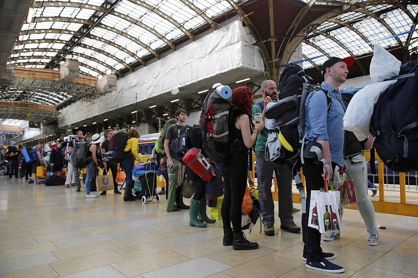 People waiting to board a train at Paddington Station in London.