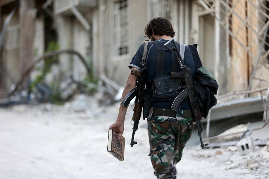 A Free Syrian Army fighter walks along a street in Jobar, a suburb of Damascus.