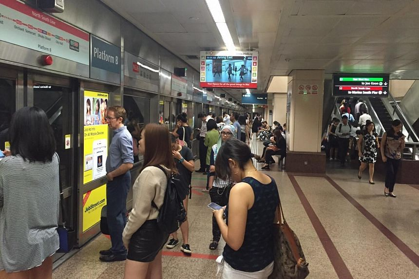 Commuters at Raffles Place MRT station on Wednesday, July 8, 2015.