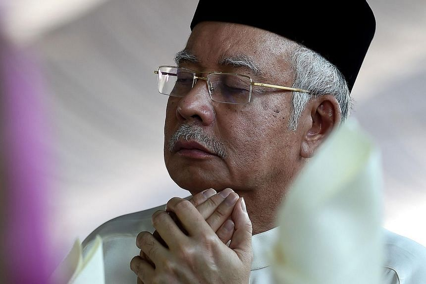 Malaysia's Prime Minister Najib Razak offers a prayer during a Ramadan Iftar gathering at a mosque in Semenyih.
