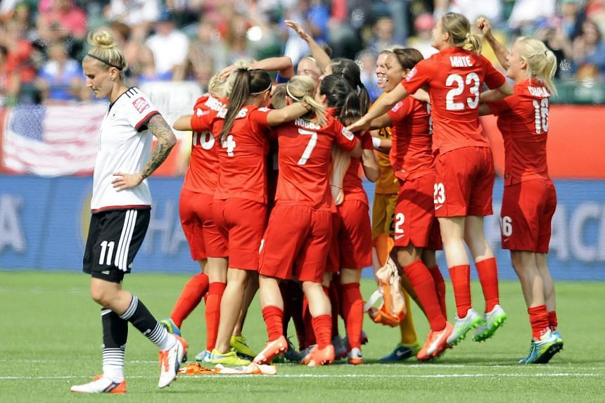 England players celebrate their win as Germany's Anja Mittag (left) walks off the pitch following the Fifa Women's World Cup 2015 match for third place between England and German.