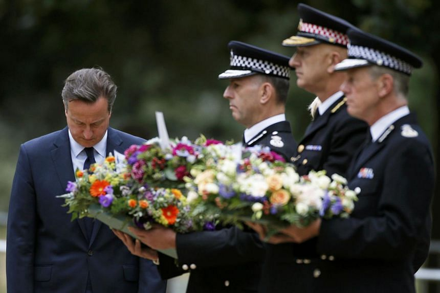 British Premier David Cameron with police officers at a memorial at Hyde Park for victims of the July 7, 2005 London bombings yesterday.