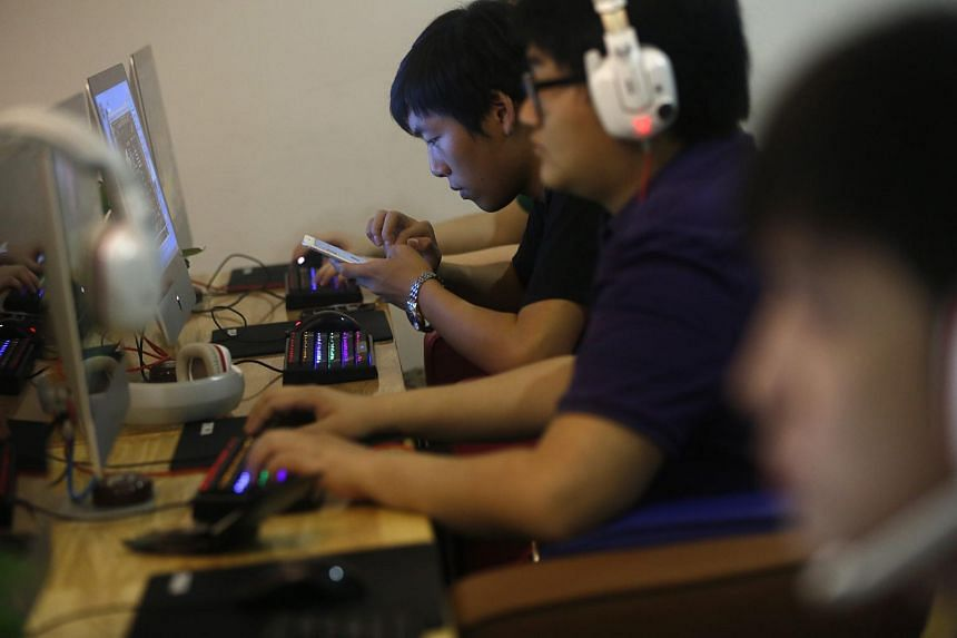 A Chinese man uses his mobile phone at an internet cafe in Beijing, China, June 26, 2015.