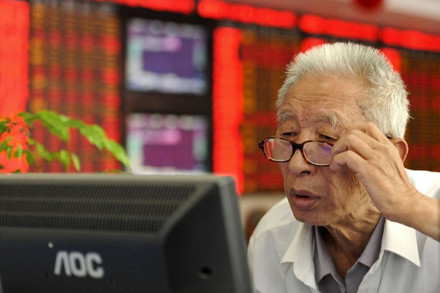 An investor adjusts his glasses as he looks at a computer screen in front of an electronic board showing stock information at a brokerage house in Fuyang, Anhui province, China, on July 9, 2015.
