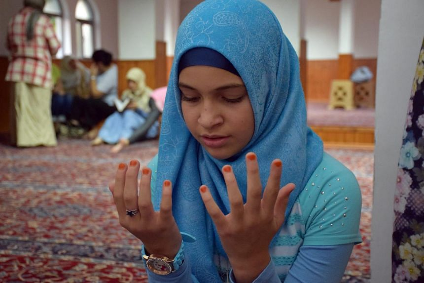 An Albanian girl prays at the Dine Hoxha mosque during the holy month of Ramadan, in Tirana, Albania, on July 7, 2015.
