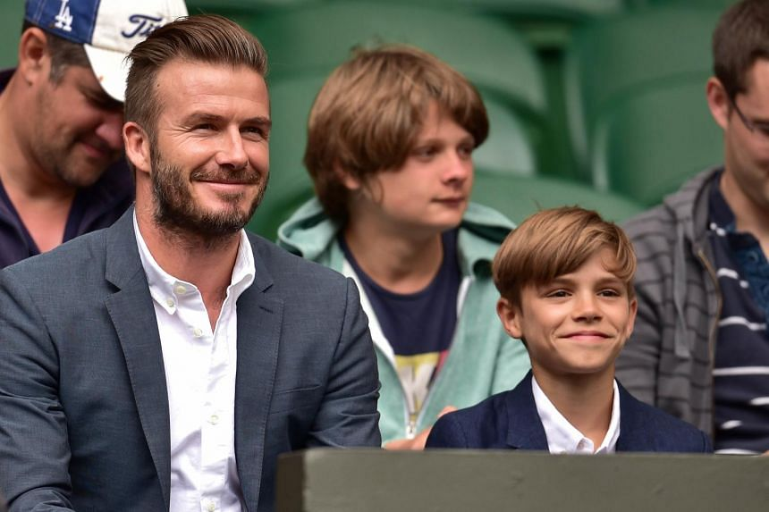 Former England footballer David Beckham (left) and his son Romeo (right) take their seats on centre court.