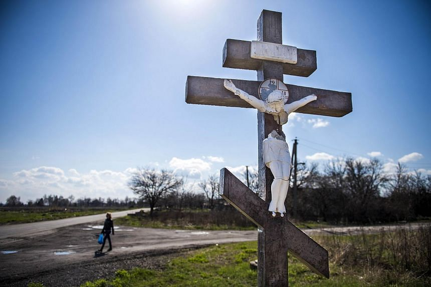 A person walks next to a crucifix partially destroyed by shrapnel on a road near the site where Malaysian Airlines flight MH17 was shot out of the sky.