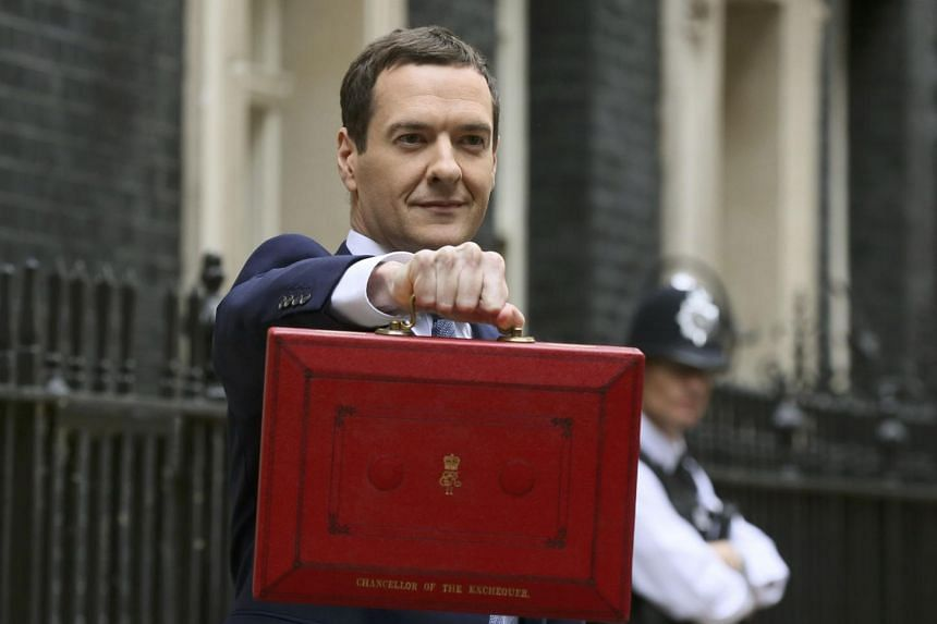 Chancellor George Osborne holds up his budget case for the cameras.