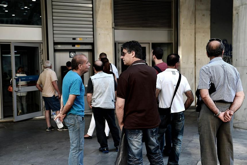 People queue outside a bank to withdraw cash from an ATM in Athens on July 7, 2015.