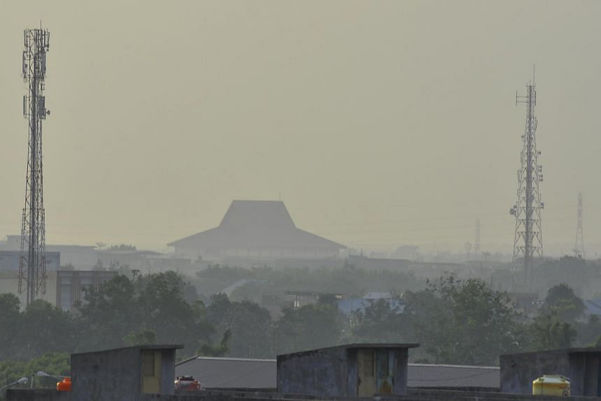 Pekanbaru, Riau, shrouded in haze yesterday. Local officials began distributing masks, while visibility at the Pekanbaru airport fell to as low as 600m, resulting in a flight being diverted to Batam.