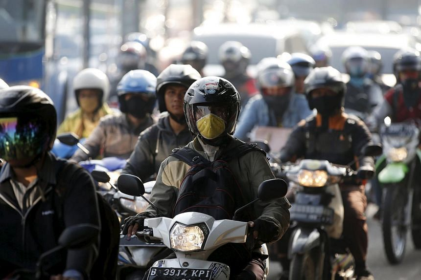 Motorcyclists on a road in Jakarta.