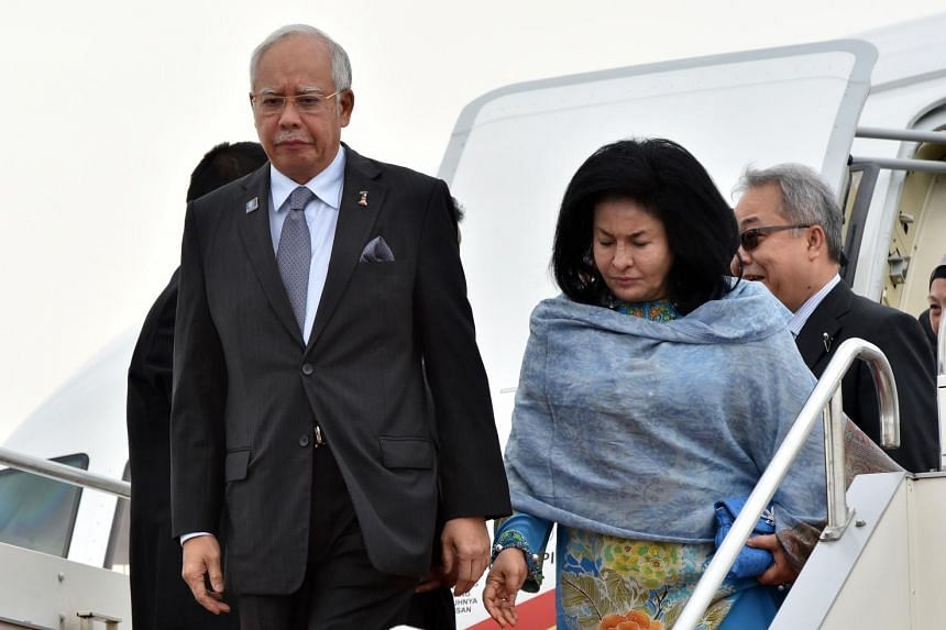Malaysian Prime Minister Najib Razak (left) and his wife Rosmah Mansor (right) arrive at the airport in Tokyo on May 24, 2015.