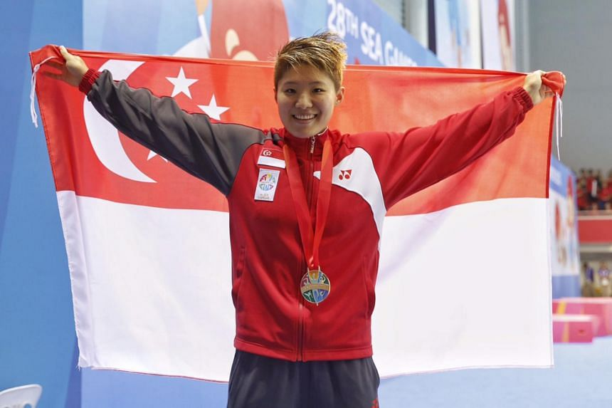 Singapore's Tao Li poses for a photo after winning the women's 100m backstroke at the 28th SEA Games at OCBC Aquatic Centre on on June 9, 2015.