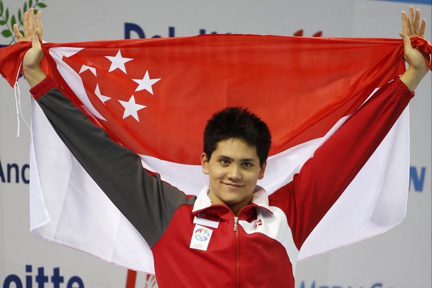 Singapore's Joseph Schooling on the podium after winning the men's 50m butterfly at the 28th Sea Games swimming meet at the OCBC Aquatic Centre on June 10, 2015.