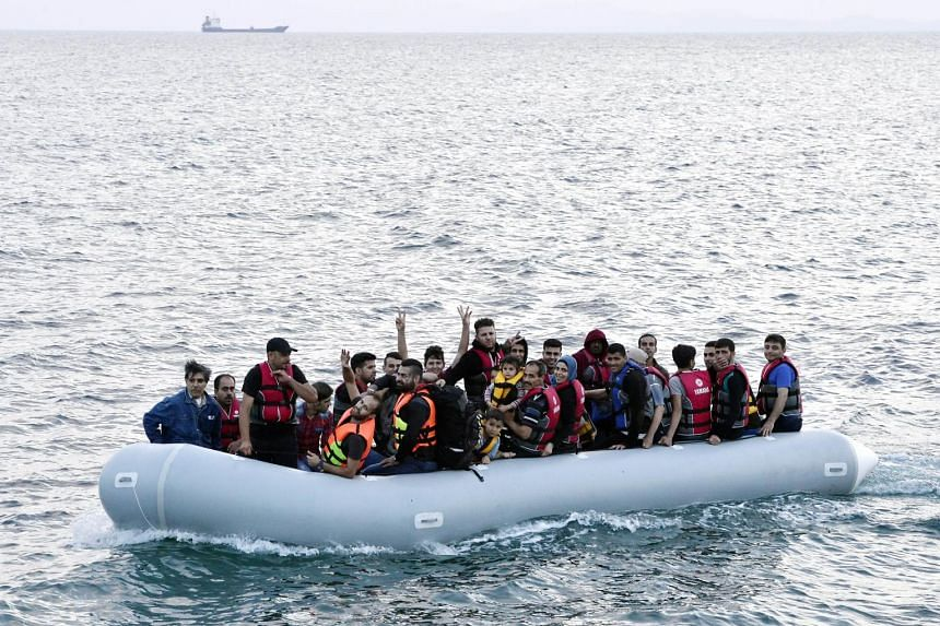 Migrants on an overcrowded dinghy arrive on the coast of Lesbos island on June 18, 2015.