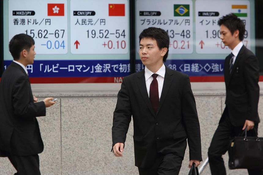 Pedestrians walk past an electronic board displaying exchange rates on July 9, 2015.