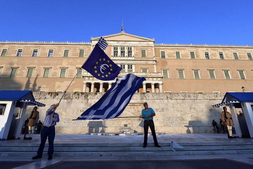 Pro-European Union protesters wave EU and Greek flags in front of the Greek parliament in Athens on July 9, 2015.