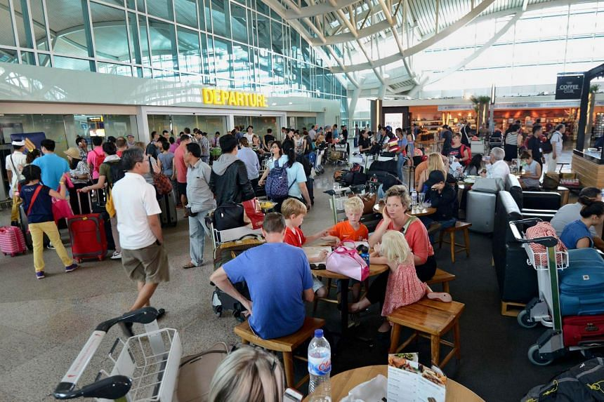 Passengers sit around the international terminal at Bali's Ngurah Rai airport in Denpasar waiting for information of flight delays due to volcanic ash near Indonesia's resort island on July 10, 2015.