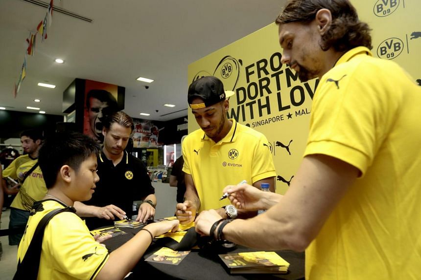 Former midfielder Lars Ricken (2nd left), forward Pierre-Emerick Aubameyang (centre) and defender Neven Subotic (right) sign autographs in Singapore on July 10, 2015.