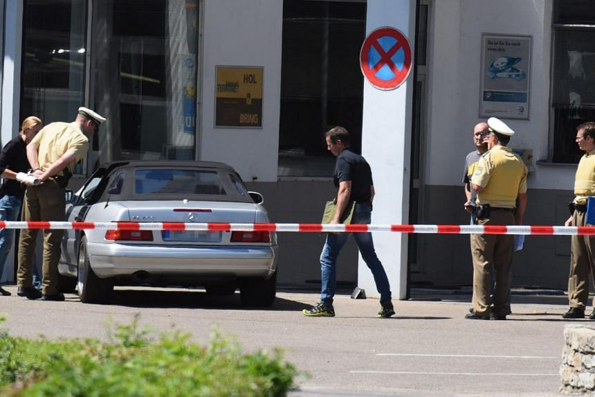 Police stand around the car driven by the gunman, at a petrol station in Bad Windsheim, Germany, on July 10, 2015.