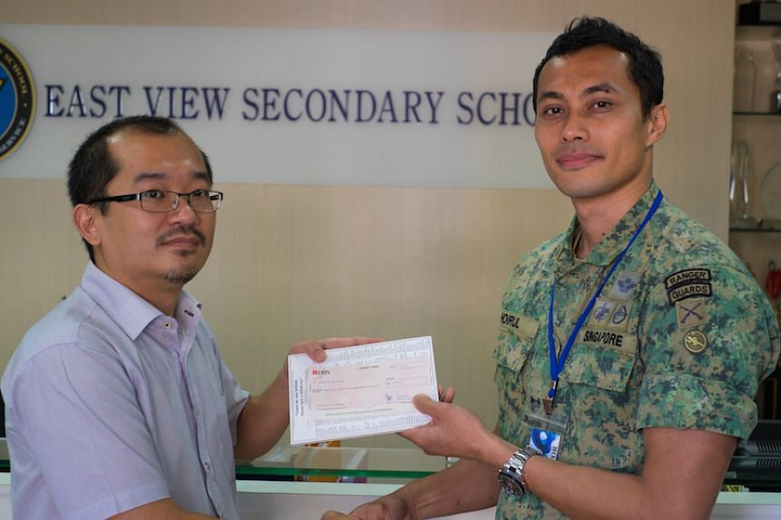 Mr Hoirul Hafiidz (right), one of the fund-raisers, presenting a cheque to Mr Chua Wee Nam from East View Secondary School. Mr Chua was the primary liaison for the fund-raising campaign.