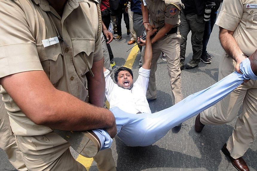 Police detaining a Youth Congress activist protesting near a Bharatiya Janata Party office in Madhya Pradesh on Wednesday against the government recruitment and admission scam.