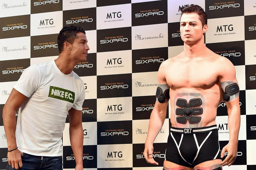 A bemused Cristiano Ronaldo inspects his look-alike figure made by a 3D printer, which is equipped with the Training Gear Sixpad designed by the Portuguese star.