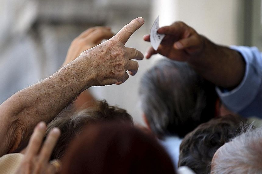 """Pensioners raising their hands for priority tickets to receive part of their pensions in front of the main entrance of a National Bank branch in central Athens yesterday. ECB president Mario Draghi has characterised the Greek situation as """"really dif"""