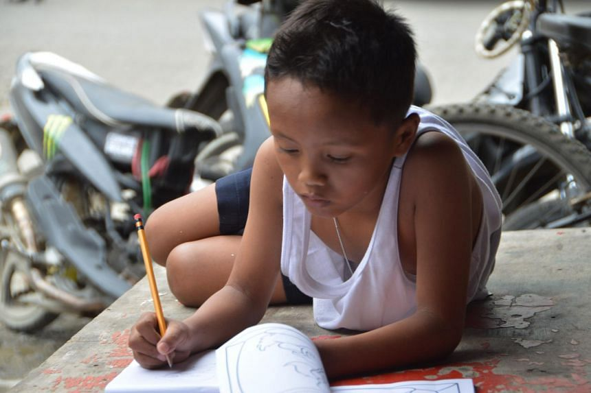 Daniel Cabrera doing his homework on a pavement in Mandaue City, central Philippines.