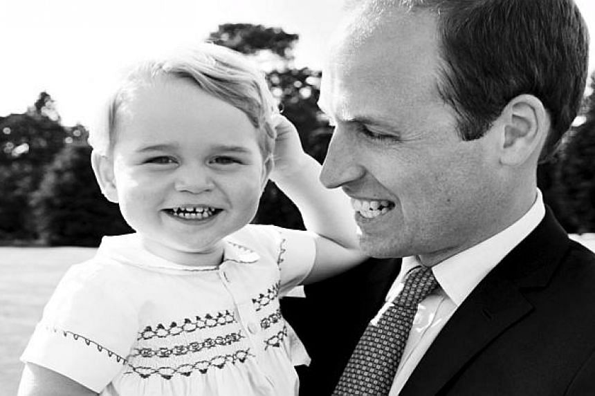 Britain's Prince William holds his son, Prince George, after the christening of Princess Charlotte.