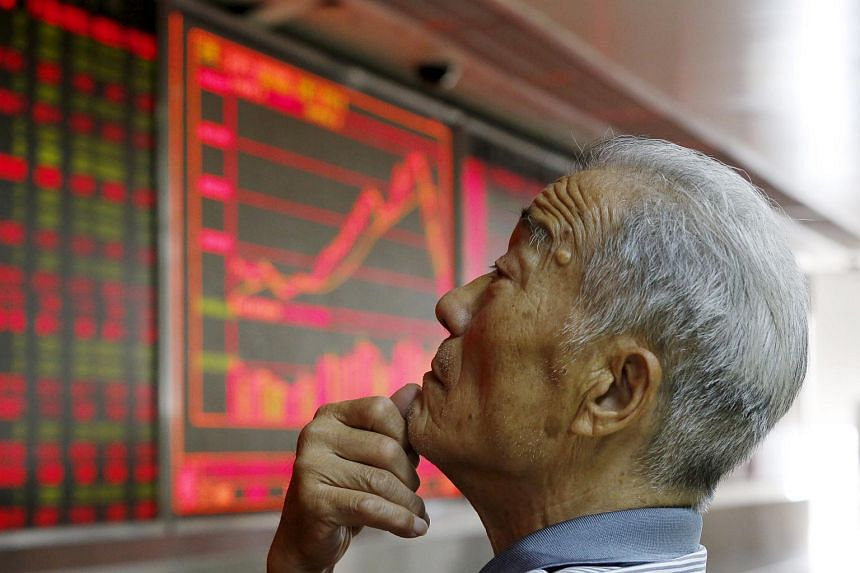 An investor watching an electronic board showing stock information at a brokerage office in Beijing, China.