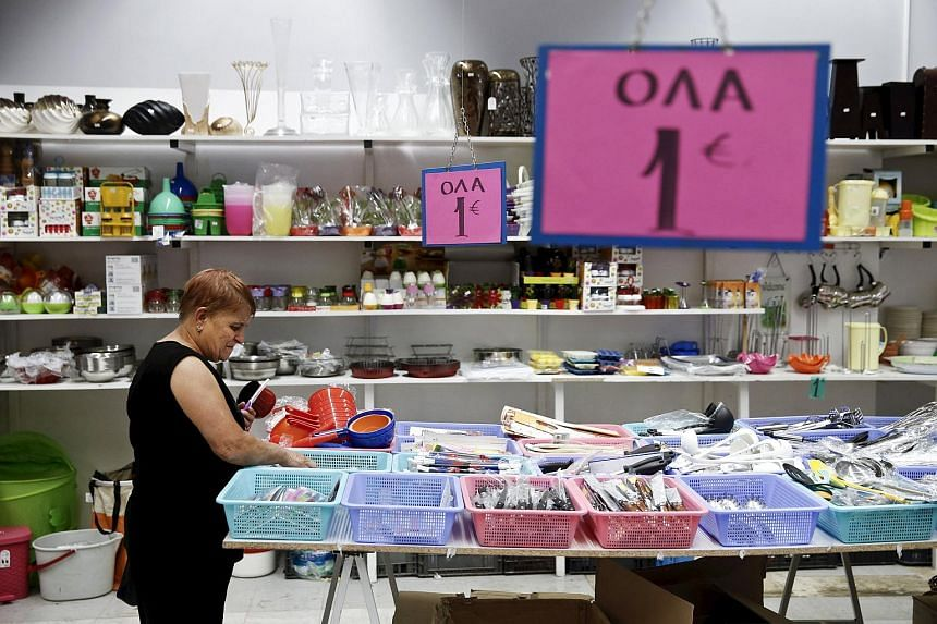 A woman looking at goods displayed for sale inside a one-Euro shop in Athens.