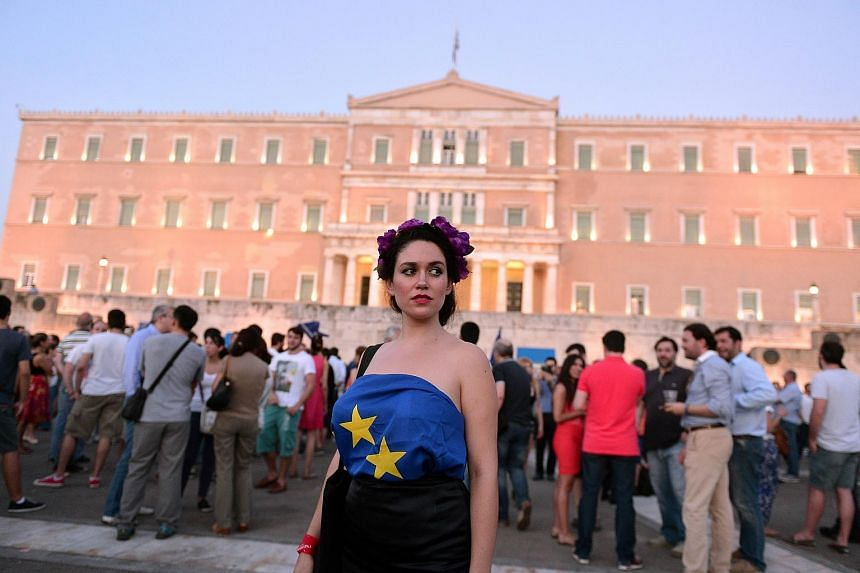 A pro-European Union protester wearing an EU flag in front of the Greek parliament.