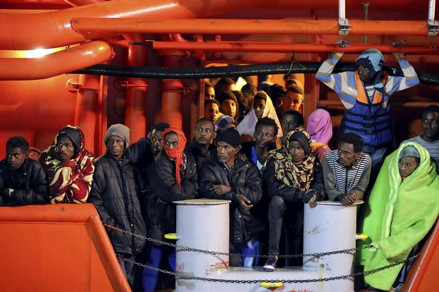 Migrants wait to disembark from a tugboat in Pozzallo, southern Italy.