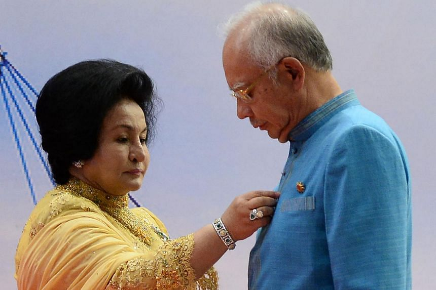 Rosmah Mansor (left), wife of Malaysian PM Najib Razak (right), adjusting his shirt as they wait for a group photo during the Asean Summit in Kuala Lumpur.