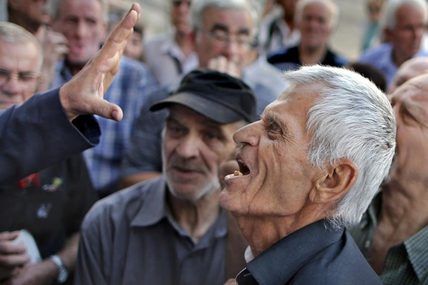 A pensioner argues with an official as he tries to enter a National Bank branch to receive part of his pension in Athens, Greece, on July 6, 2015. Greece has submitted to its eurozone creditors a new bailout plan.  PHOTO: REUTERS