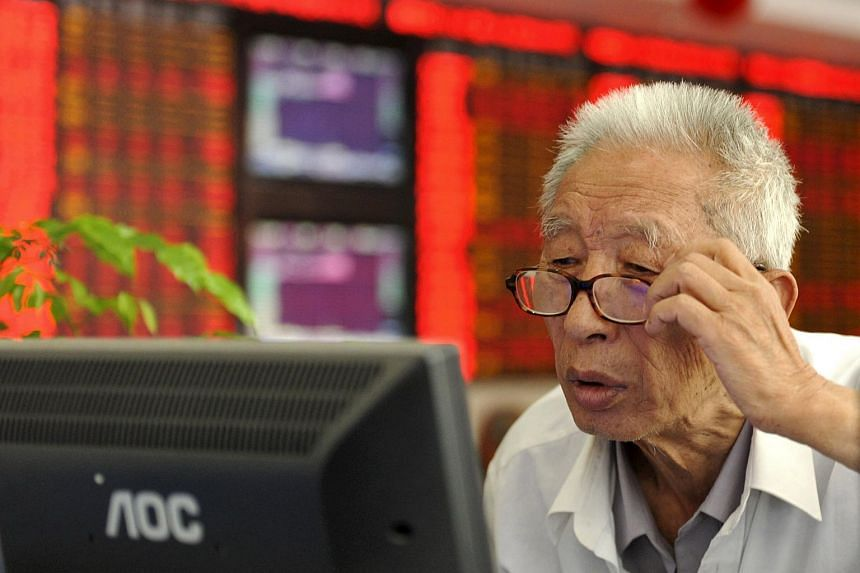 An investor in front of an electronic board showing stock information in Fuyang, China, on July 9, 2015.