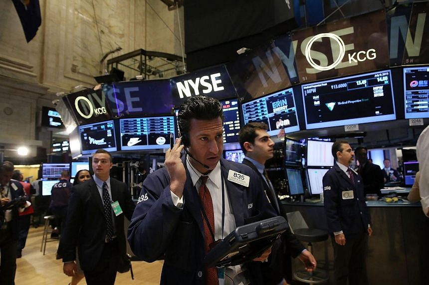 """Traders working on the floor of the NYSE a day after the market closed for over three hours due to a """"technical glitch""""."""