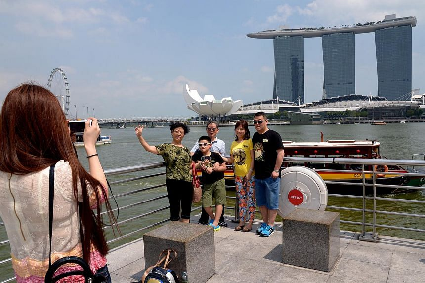 A group of tourists from China posing for a photograph in Singapore.