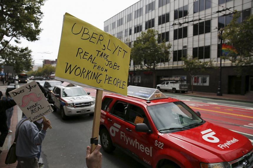 Members of the San Francisco Taxi Workers Association carrying signs at a rally at Uber headquarters.