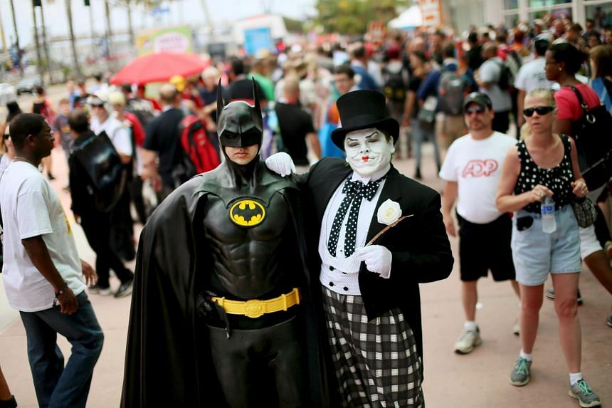 Comic-Con convention goers dressed as Batman and the Joker pose for pictures outside of the 2015 Comic-Con International in San Diego, California on July 10, 2015.