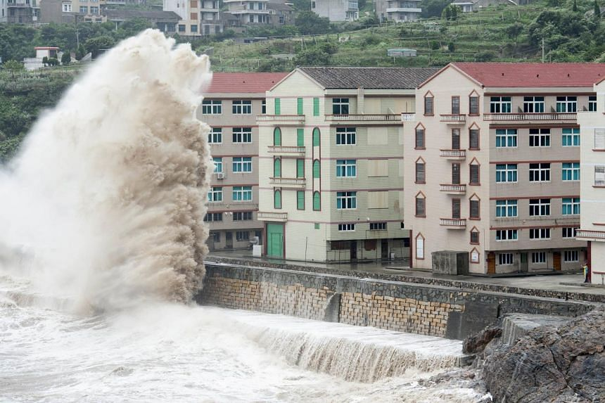 A wave, under the influence of typhoon Chan-hom, hits the shore next to residential buildings in Wenling, Zhejiang province, China on July 10, 2015.