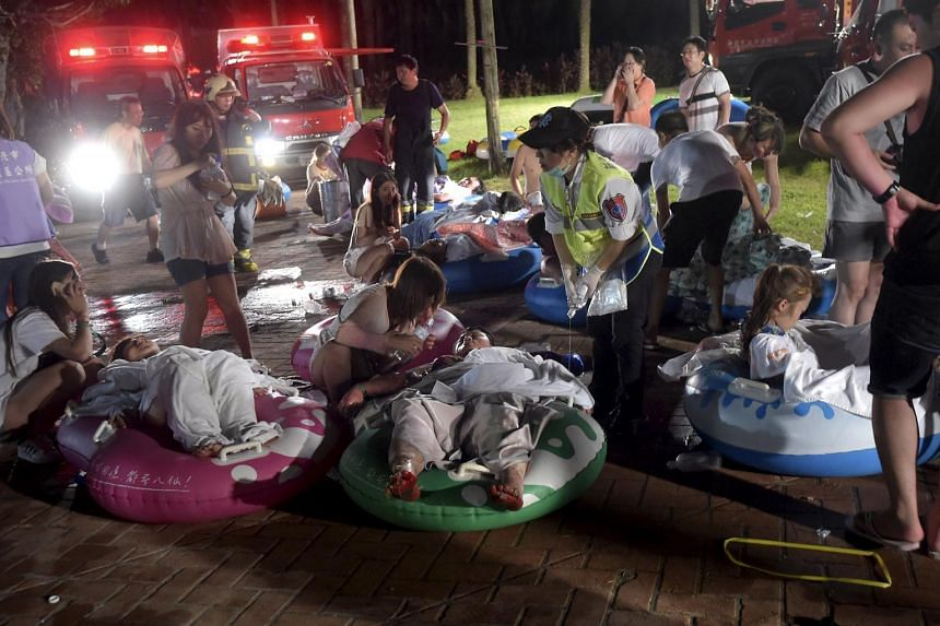 Injured victims from an accidental explosion during a music concert lie on the ground at the Formosa Water Park in New Taipei City, Taiwan, on June 27, 2015.