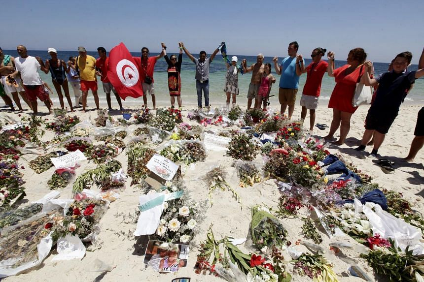 People join hands as they observe a minute's silence in memory of those killed in a recent attack by an Islamist gunman, at a beach in Sousse, Tunisia on July 3, 2015.