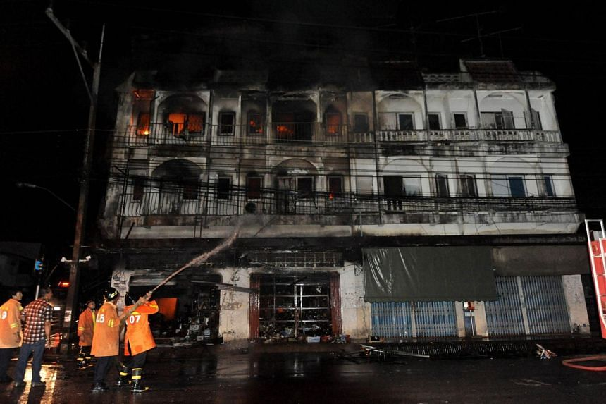 Thai firefighters spray water on burning buildings following a bomb blast attack by suspected separatist militants in Sungai Kolok, in Thailand's restive southern province of Narathiwat.