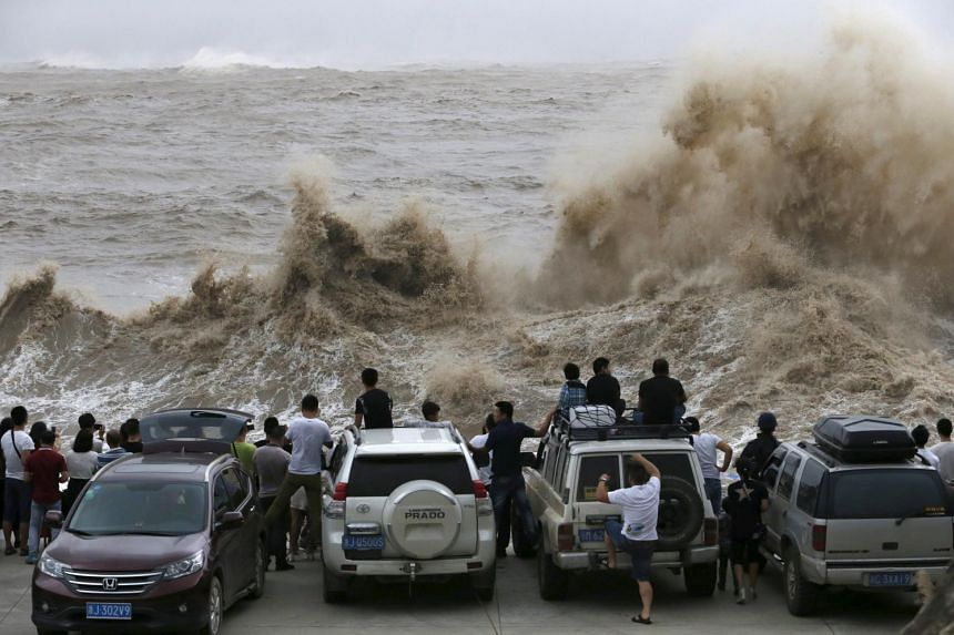 People look on as waves, under the influence of typhoon Chan-hom, hit the shore in Wenling, Zhejiang province, China on July 10, 2015.