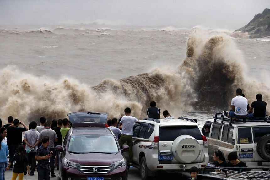 People gather on the bank to watch huge waves as typhoon Chan-hom comes near Wenling, east China's Zhejiang province on July 10, 2015.