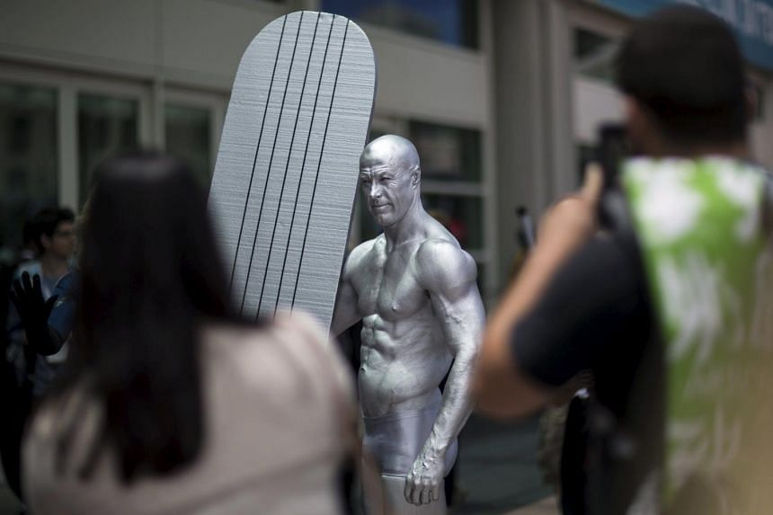 A cosplay enthusiast dressed like the character Silver Surfer poses for photos during the 2015 Comic-Con International Convention on July 10, 2015.