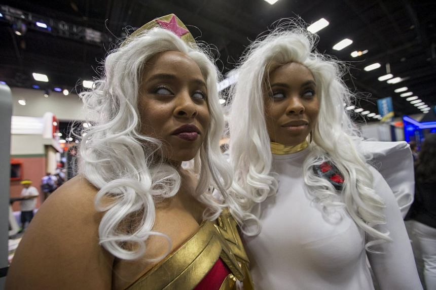 Cosplay enthusiasts Liz (left) and Ruth wear costumes of Wonder Woman and Storm from the X-Men, during the 2015 Comic-Con International Convention in San Diego, California on July 10, 2015.