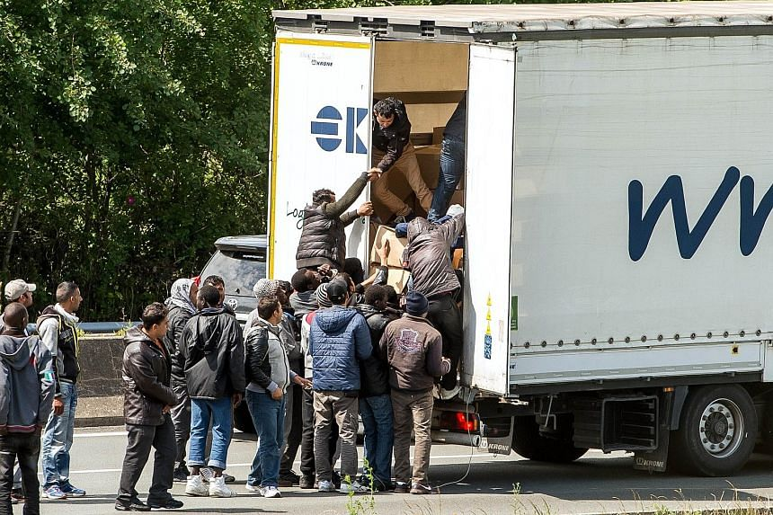 Migrants trying to climb aboard a lorry on a highway leading to the Eurotunnel, during a road blockade in Calais late last month.